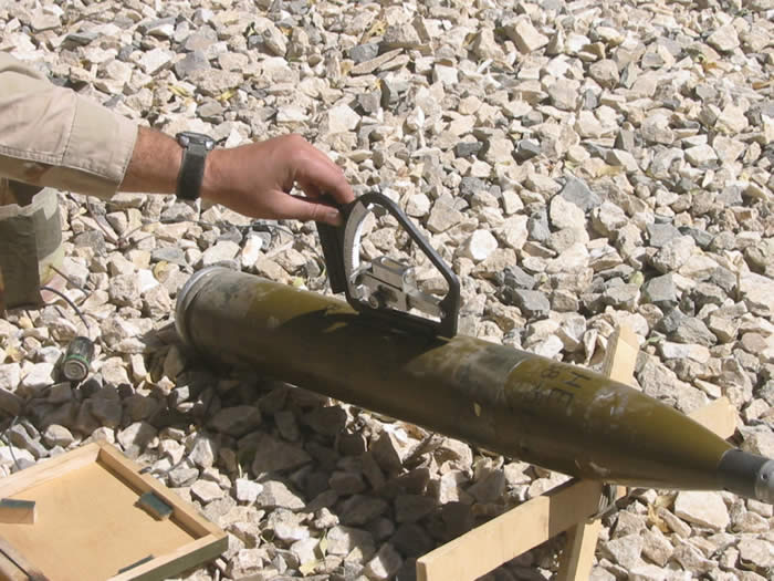 A BM12 mounted on two crossed sticks. I was using a quadrant to measure the angle. The Afghanis did not have quadrants. They tried to set the rockets up on consistent angles similar to that pictured here, which was about the max range of the rocket, 8 Kilometers, and instead of adjusting the rocket angle on the next attack they would adjust the lunch site back and fourth until they found something that worked. Note the battery and plastic jug with duck tape. The rockets are fired electronically. There are tripod mounted single guns that can fire them but more they were more commonly fired from multiple rocket launchers. The insurgents would wire the one side of the battery to the side of the jug with a loop on the end, the other side to a hook mounted on a small piece of wood or float. They would hammer a nail into the jug, fill it with water, then pull the nail out. As the water drained the piece of wood with the hook would pull lower and lower through the loop until the hook touched the loop completing the electrical connection and firing the rocket approximately 30 minutes after the insurgents left the area.